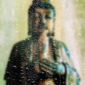 Manjushri Statue Seen Through Raindrops on a Window